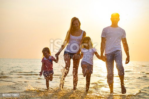849648098 istock photo Happy young family having fun running on beach at sunset. 622527662