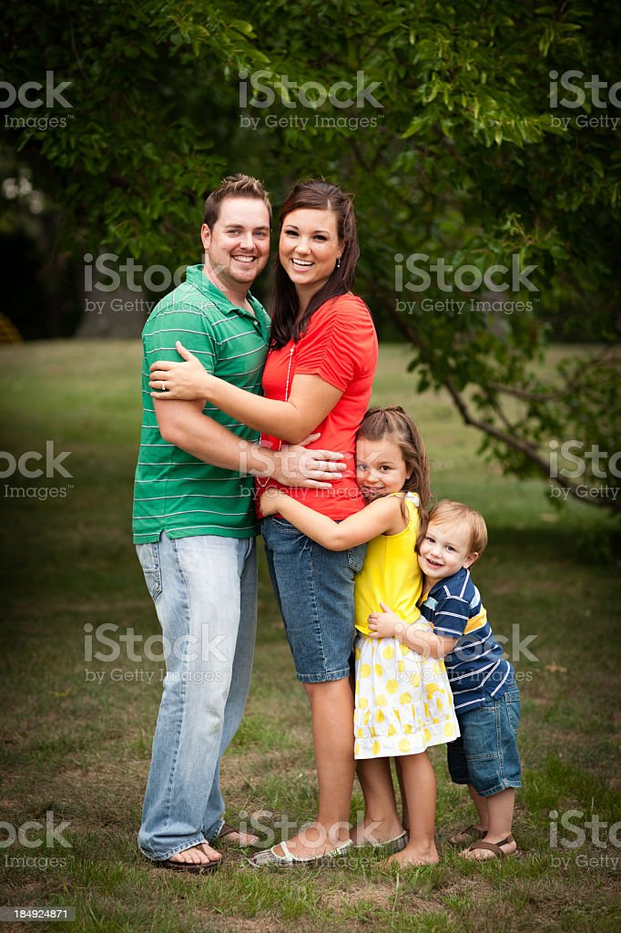 Happy Young Family Hugging Each Other in Outdoor Setting royalty-free stock photo