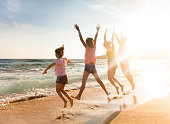 happy young family jumping on beach at sunset
