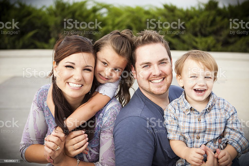 Happy Young Family Laughing Together Outside royalty-free stock photo