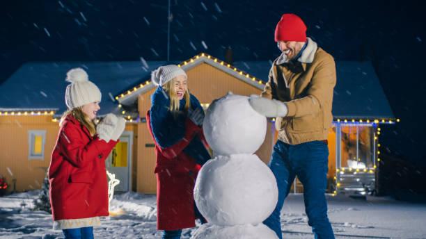 happy young familie machen schneemann in ihrer idyllischen haus. vater rollen schneeball und legt sie übereinander, tochter und frau ihm helfen. familie verbringen zeit zusammen einen winterabend. - schneemann bauen stock-fotos und bilder