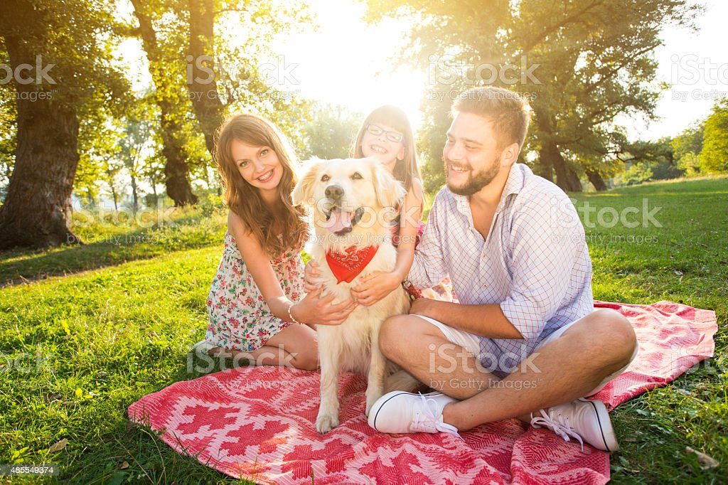 Happy young family on a summer day with their dog stock photo
