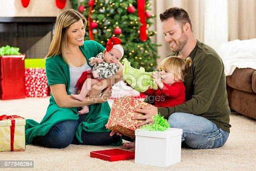 579124316 istock photo Happy young family open gifts on Christmas morning 577348284