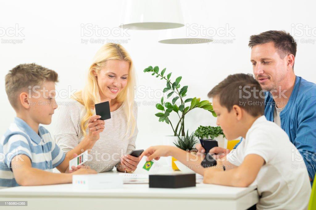 Glückliche junge Familie spielen Kartenspiel am Esstisch im hellen modernen Haus. - Lizenzfrei Beide Elternteile Stock-Foto