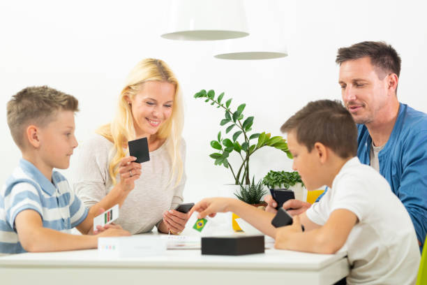 Glückliche junge Familie spielen Kartenspiel am Esstisch im hellen modernen Haus. – Foto