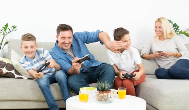 Glückliche junge Familie spielt Videospiel im Fernsehen. – Foto