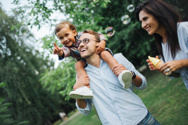Happy young family playing with bubble wands in park outdoors stock photo