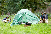 Happy young family setting up a tent for camping - Outdoors in countryside