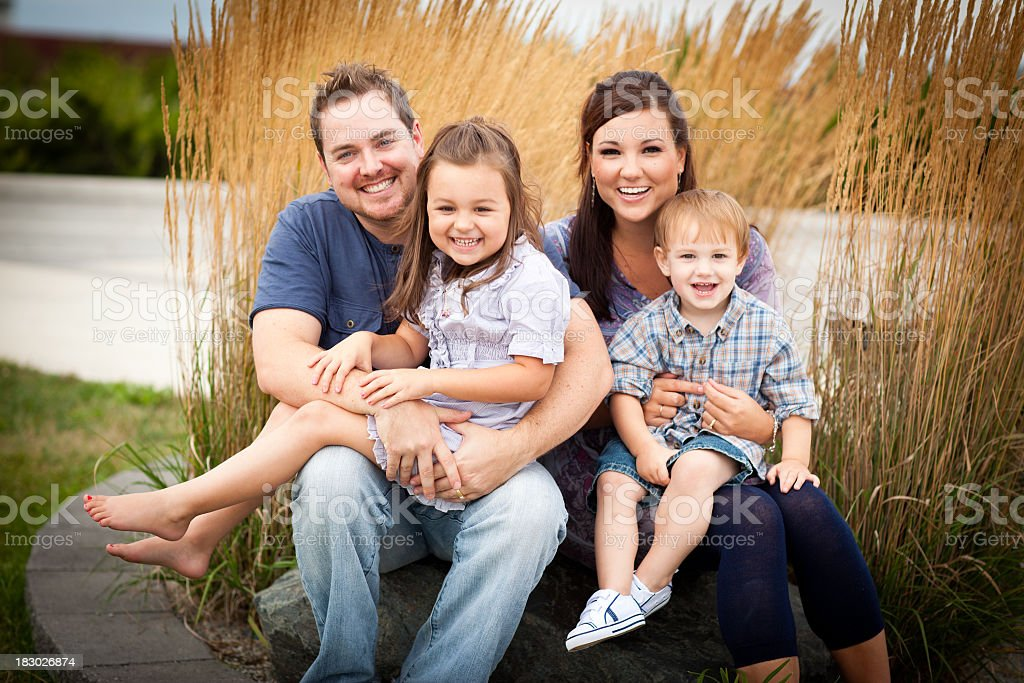 Happy Young Family Sitting Together Outside stock photo