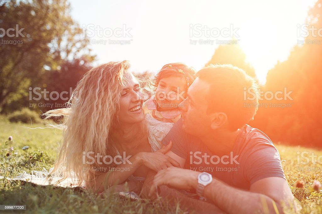 Happy young family spending time together outside in green nature. stock photo