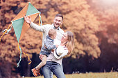 Happy family with a kite in the autumn park, having fun.