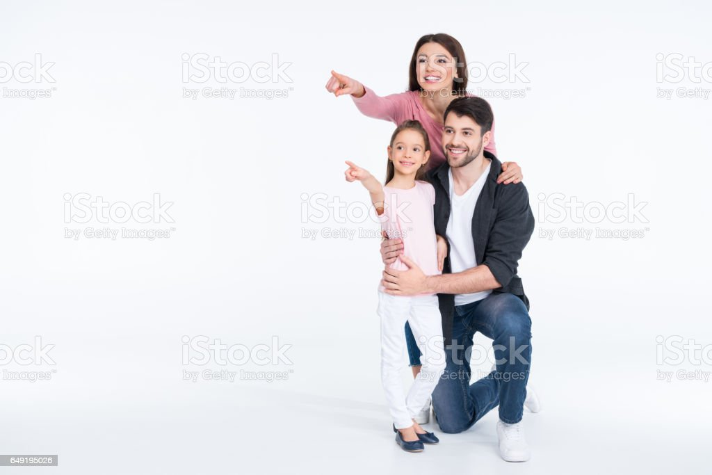 Happy young family standing together and pointing with fingers stock photo