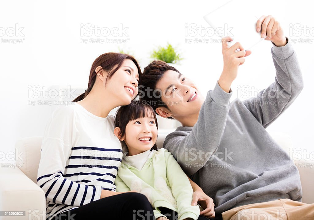 Happy young family taking selfies on sofa stock photo