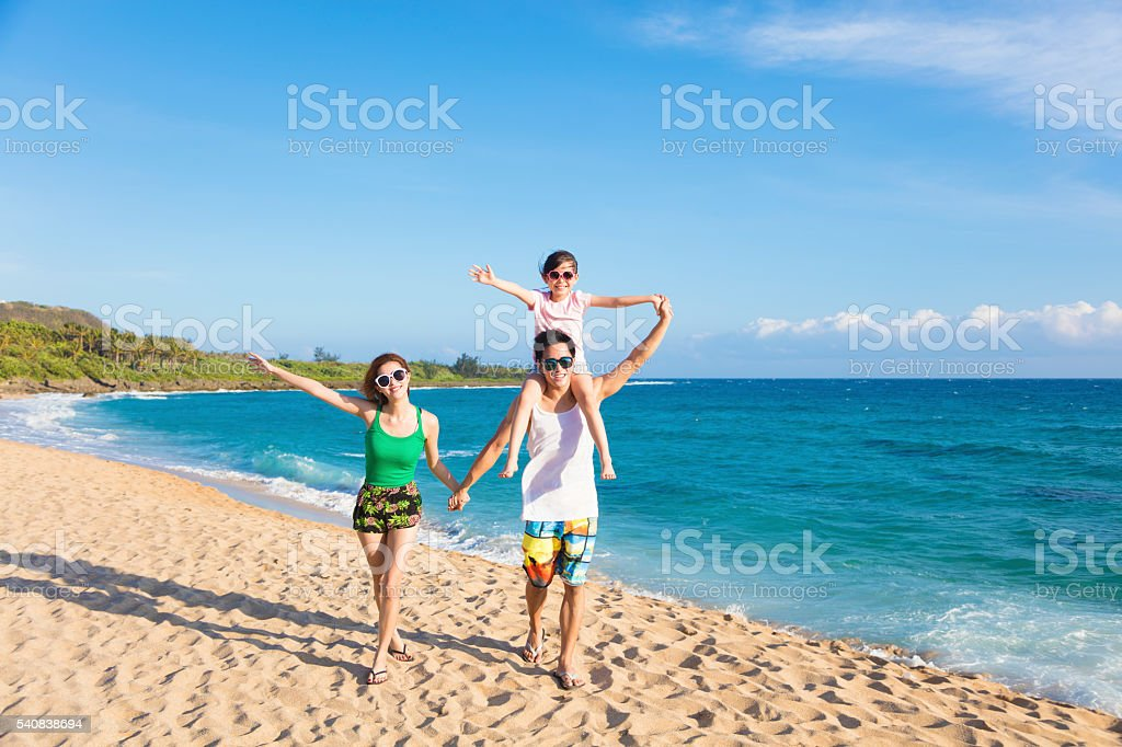 happy young family walking on the beach stock photo