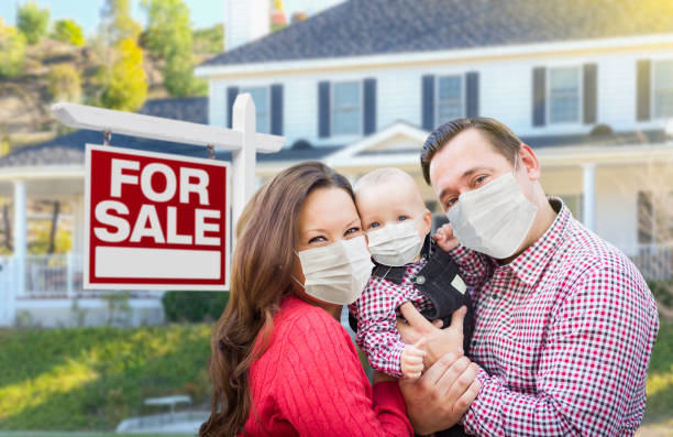 Happy Young Family Wearing Medical Face Masks In Front of New House and Sold For Sale Sign stock photo