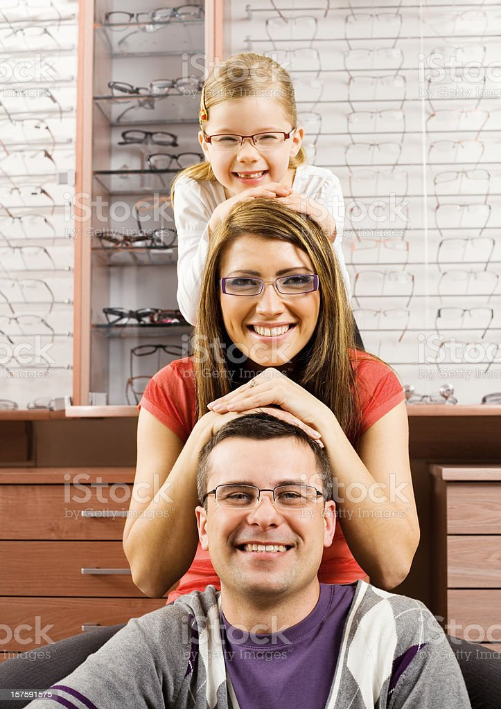Happy Young Family Wearing New Glasses Little girl posing with her father and mother, all of them wearing a new pair of glasses at the opticians. Front view, smiling at camera. 25-29 Years Stock Photo