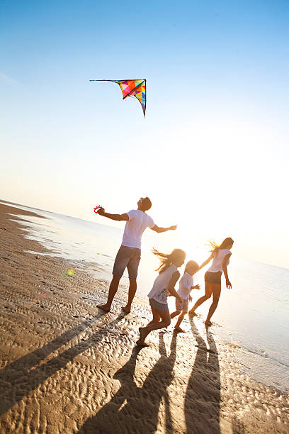 Happy young family with flying a kite on the beach - foto stock