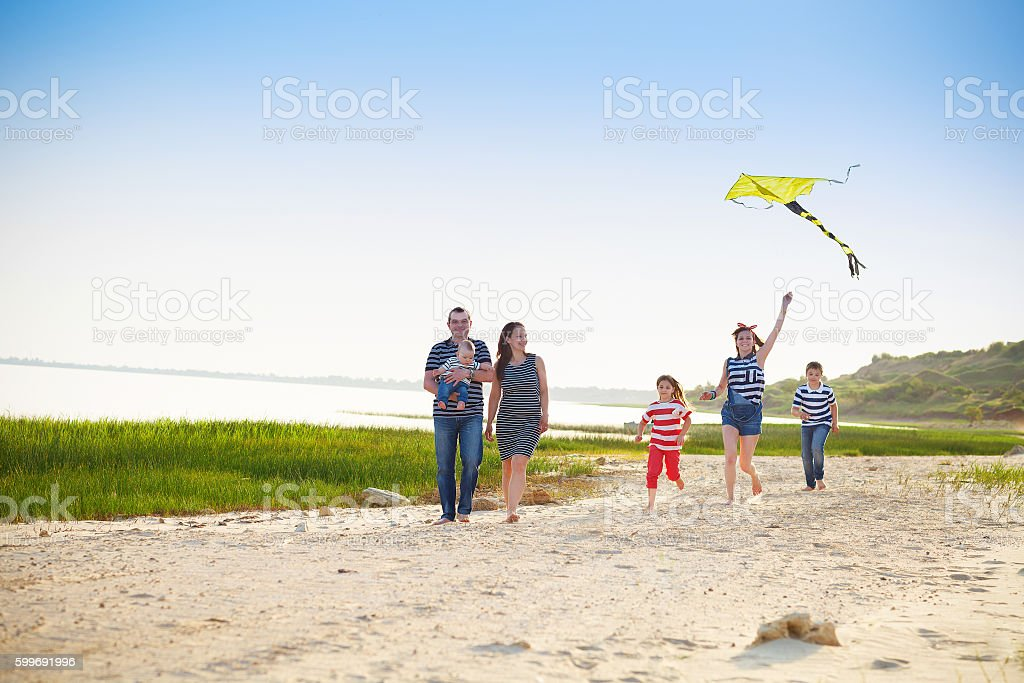 Happy young family with flying a kite on the beach stock photo