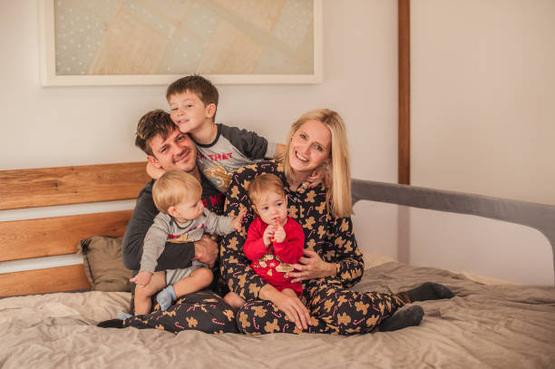 Happy Young Family with Kids on the Bed in Pajamas on Christmas Morning stock photo