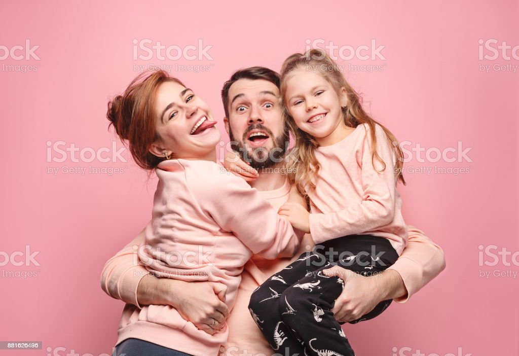 Happy young family with one little daughter posing together stock photo