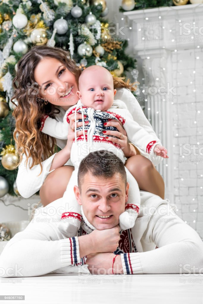 happy young family with son near Christmas fir-tree pose stock photo