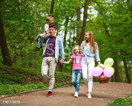 Happy young family with their two children are walking in a summer forest park, parenthood vacations with kids