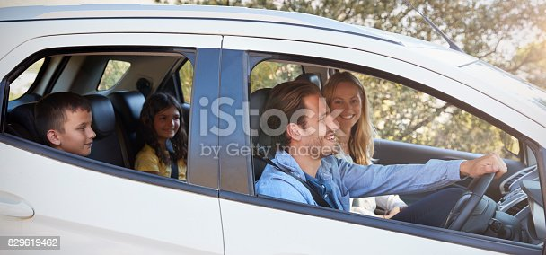 istock Happy young family with two children driving in their car 829619462