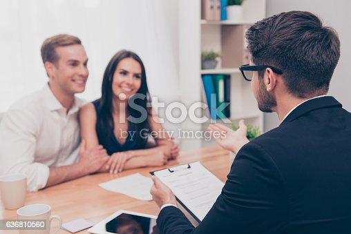 istock Happy young family working with real estate agent 636810560