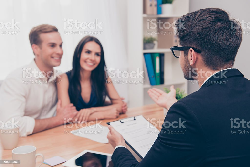 Happy young family working with real estate agent stock photo