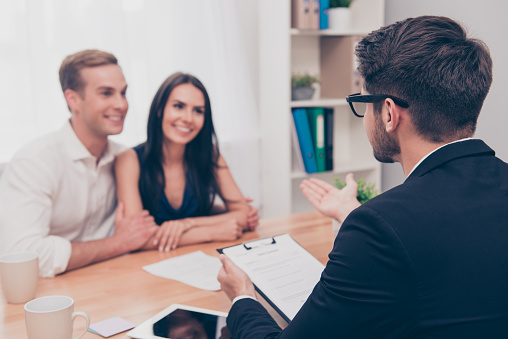 938640610 istock photo Happy young family working with real estate agent 948736846