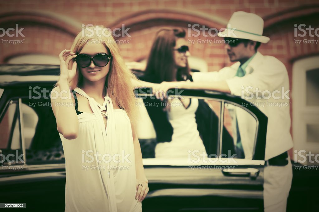 Happy young fashion blond woman in sunglasses next to retro car photo libre de droits