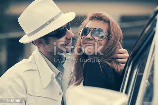 Happy young fashion couple in love leaning on vintage car  Stylish man and woman in sunglasses