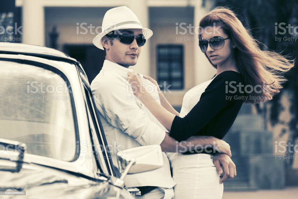Happy young fashion couple in love outside a vintage car stock photo