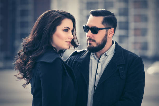 Happy young fashion couple walking on city street stock photo