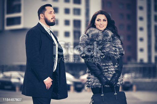 Happy young fashion couple walking on city street  Stylish trendy man in classic black coat and woman wearing fox fur jacket
