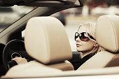 Happy young fashion woman driving convertible car