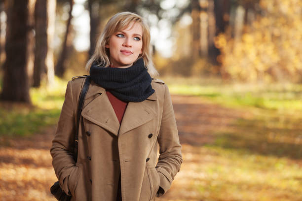 Happy young fashion woman in beige coat walking in autumn park