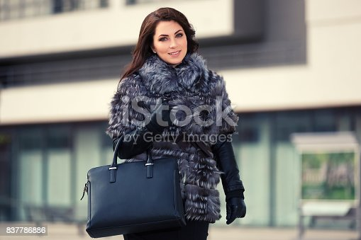 Happy young woman in fur coat coat with handbag. Stylish fashion model outdoor
