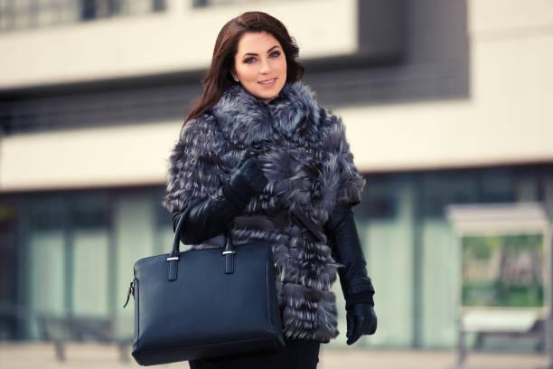 glückliche junge mode frau im pelzmantel zu fuß auf stadtstraße - winterjacke lang damen stock-fotos und bilder