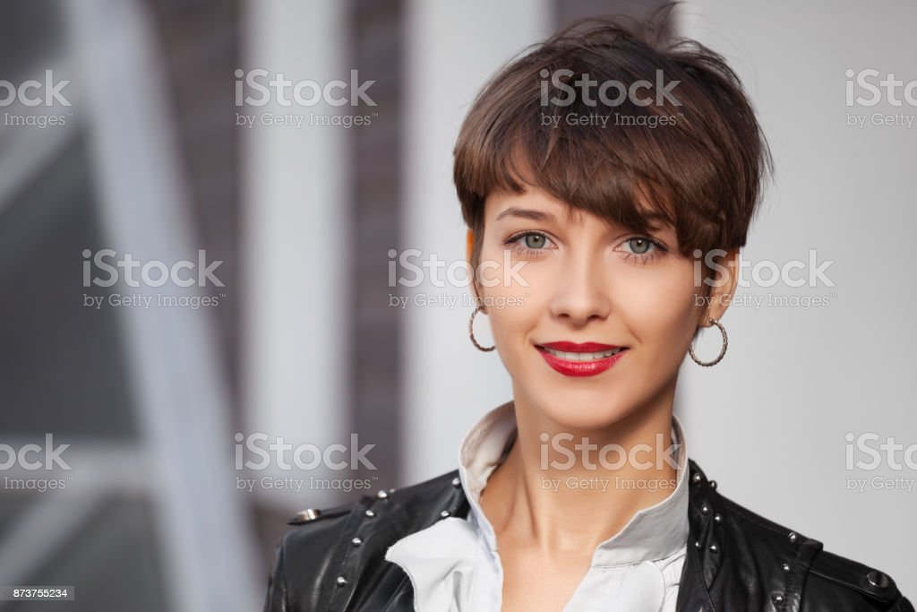 Happy young fashion woman in leather jacket walking in city street stock photo