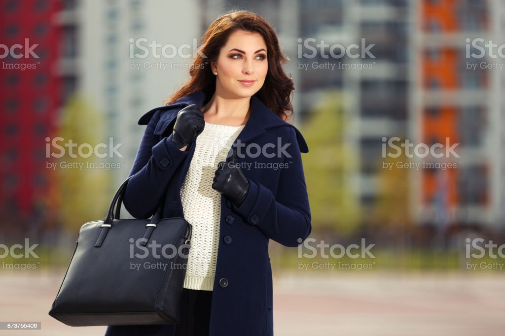 Happy young fashion woman with handbag walking in city street stock photo