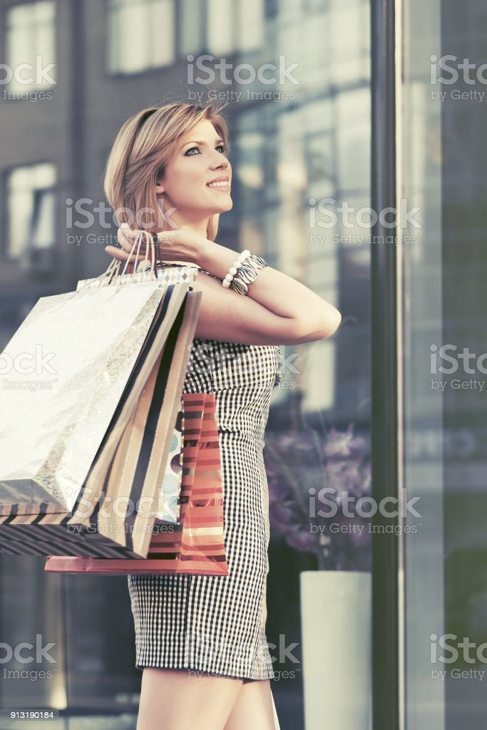 Happy young fashion woman with shopping bags walking at the mall windows stock photo