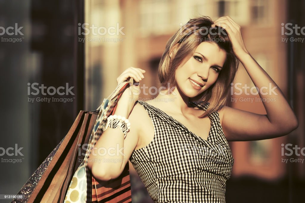 Happy young fashion woman with shopping bags walking in the mall stock photo