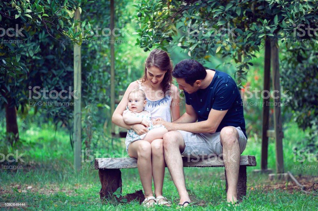 Mutlu genç baba ve anne parkta kız şirin bebek ile eğlenmek stok fotoğrafı