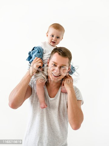 Happy young father holding son on his schoulders Smiling Handsomw young man wearing t-shirt and baby boy wearing denim jumpsuit and white t-shirt Cute family Love Care Lifestyle shot Happy guy with a kid