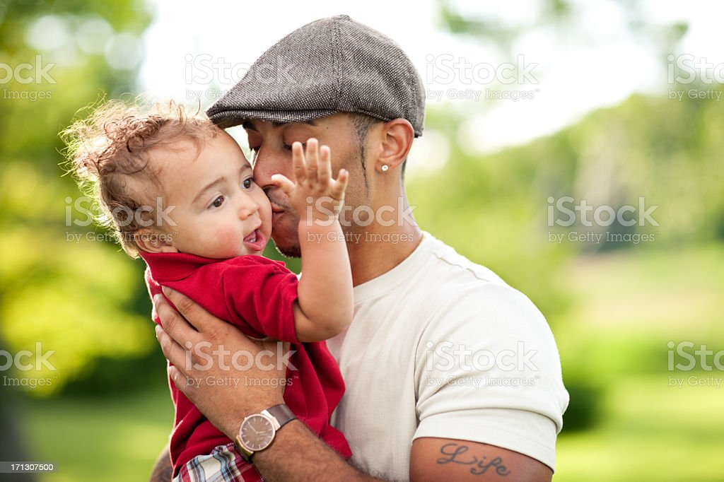 Happy, Young Father Kissing His Toddler Son Outdoors stock photo