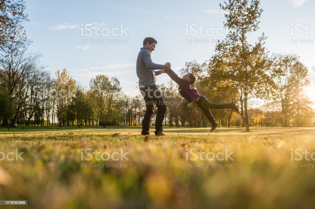 Happy young father playing with his toddler son stock photo