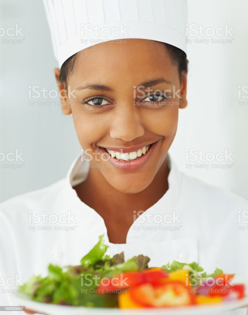 Happy young female chef holding a plate of fresh salad royalty-free stock photo
