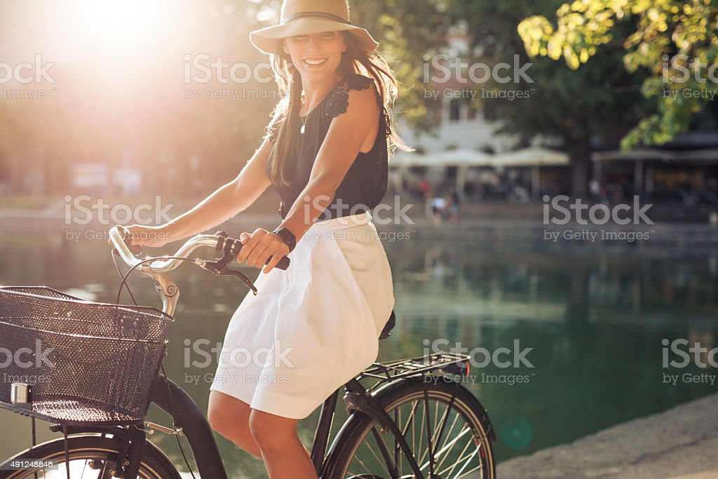 Happy young female cycling by a pond stock photo