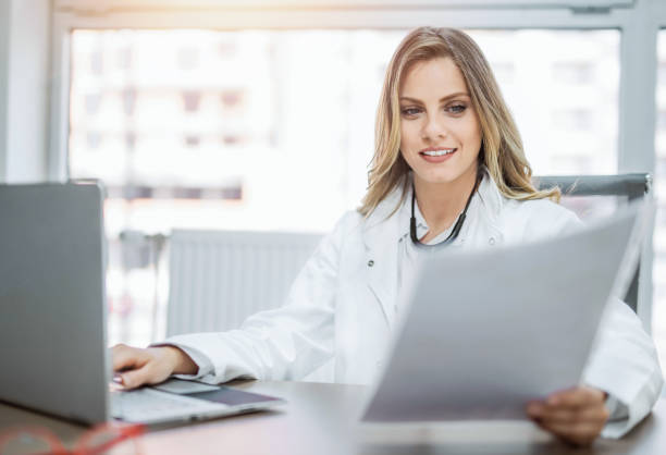 Happy young female doctor working in office. stock photo